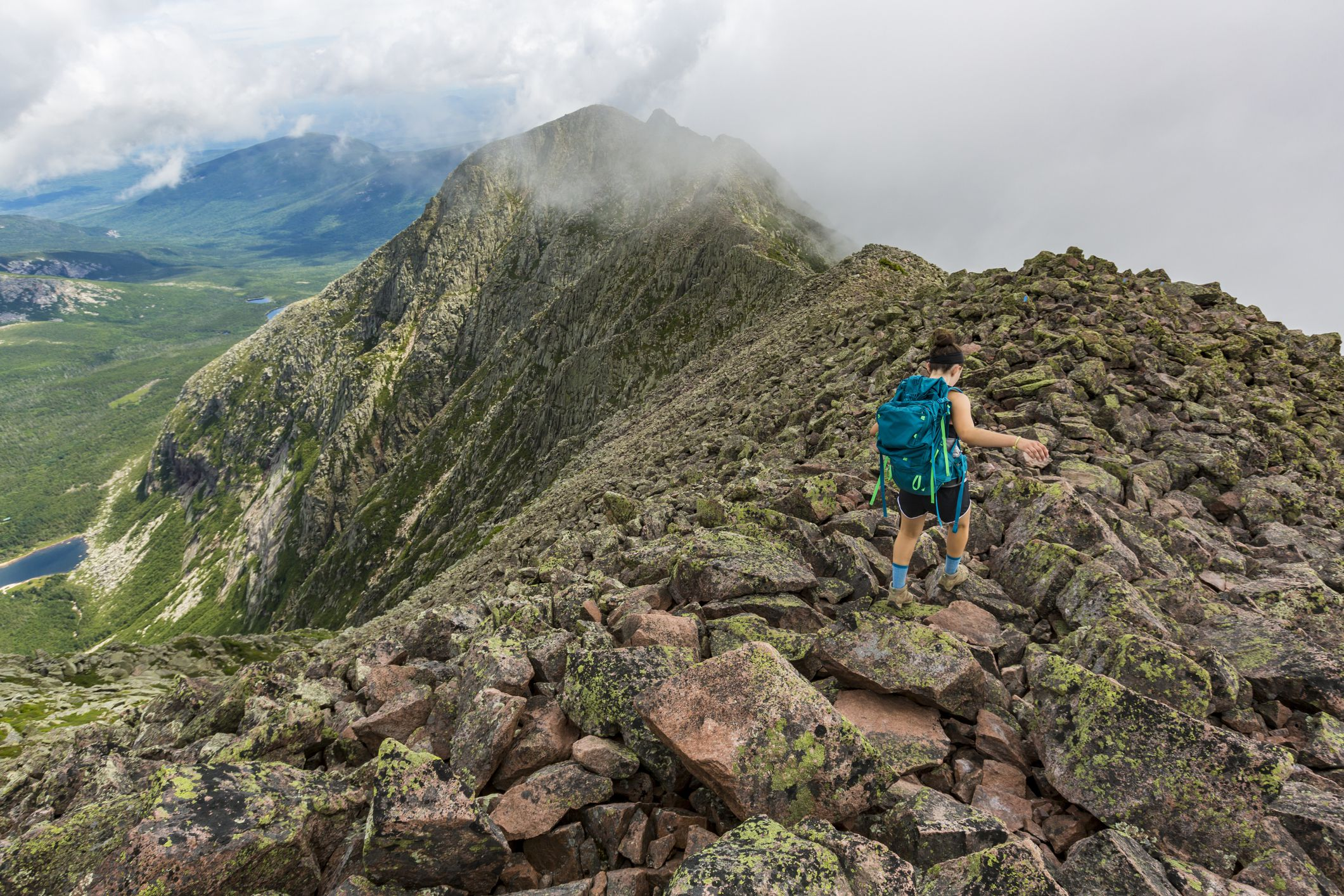 Teenage girl hiking along mountain ridge at Knife Edge Trail on Mount Katahdin in Baxter State Park, Maine, USA