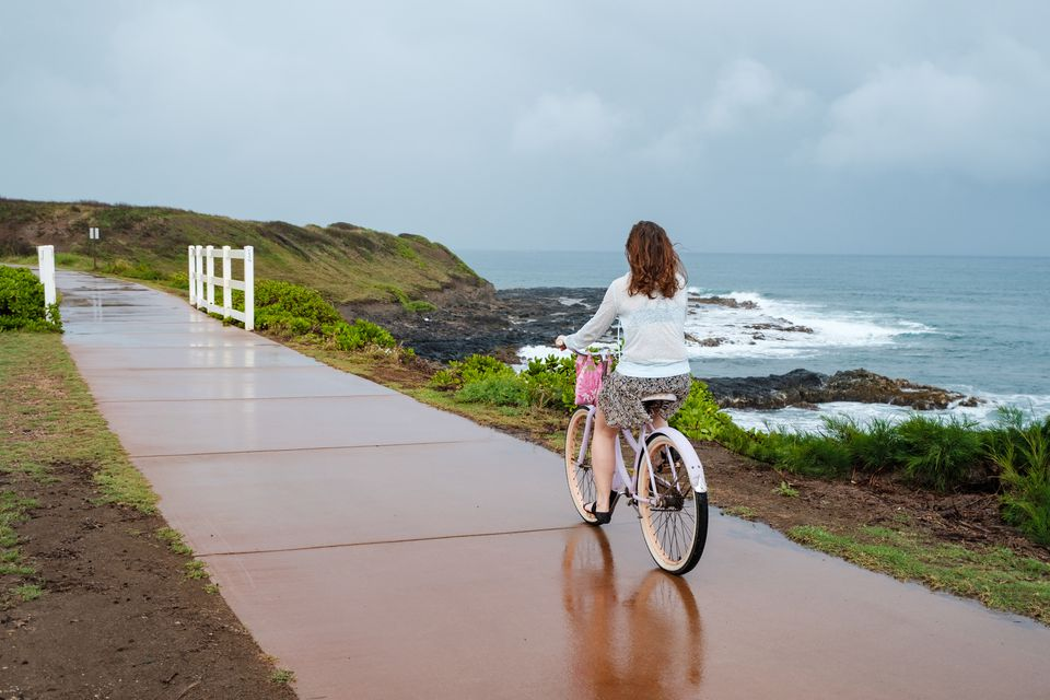 Back view of a woman riding a bicycle in the rain on Kauai