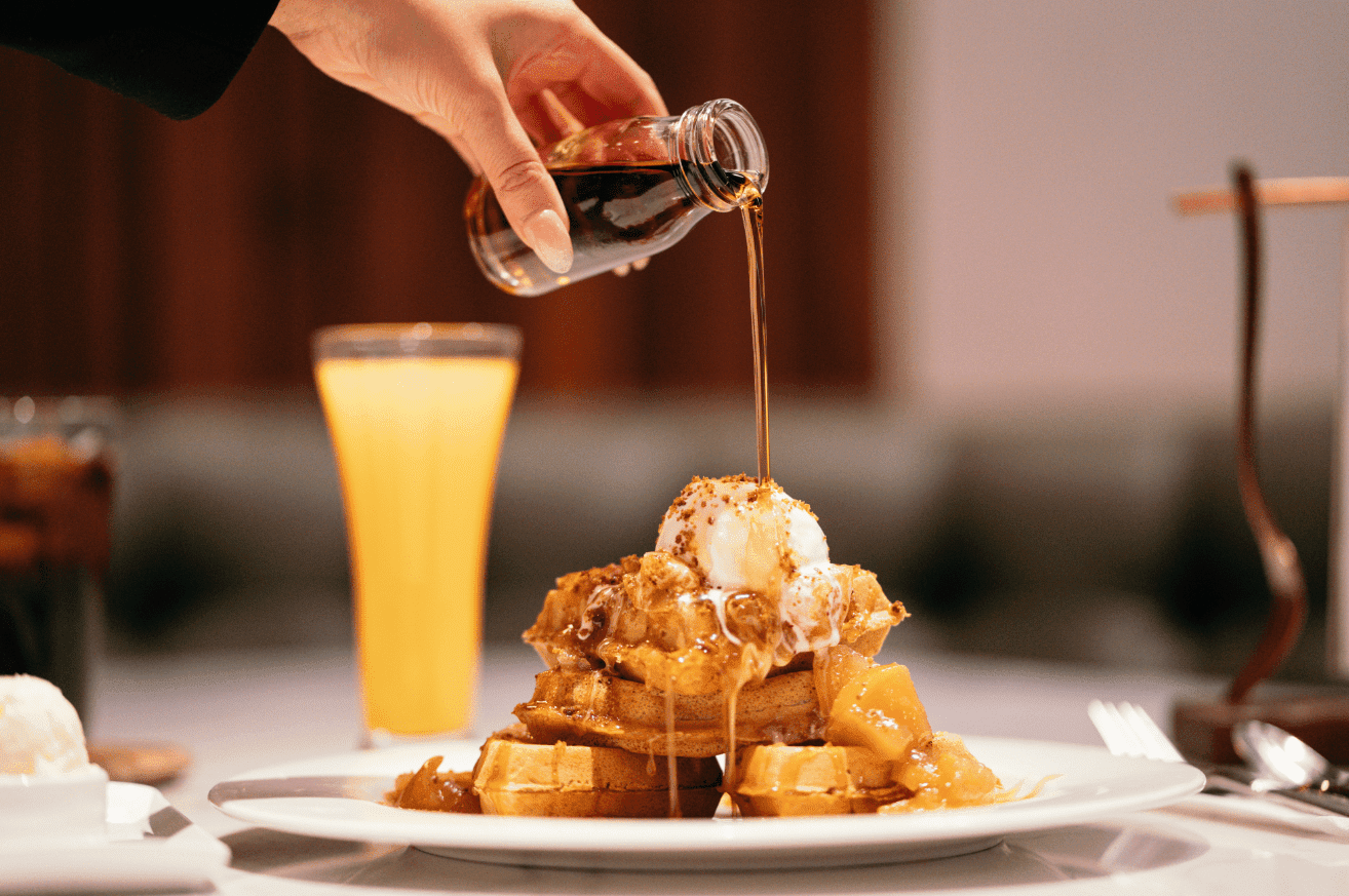 Feminine hand pouring a glass jar of syrup over four small waffles