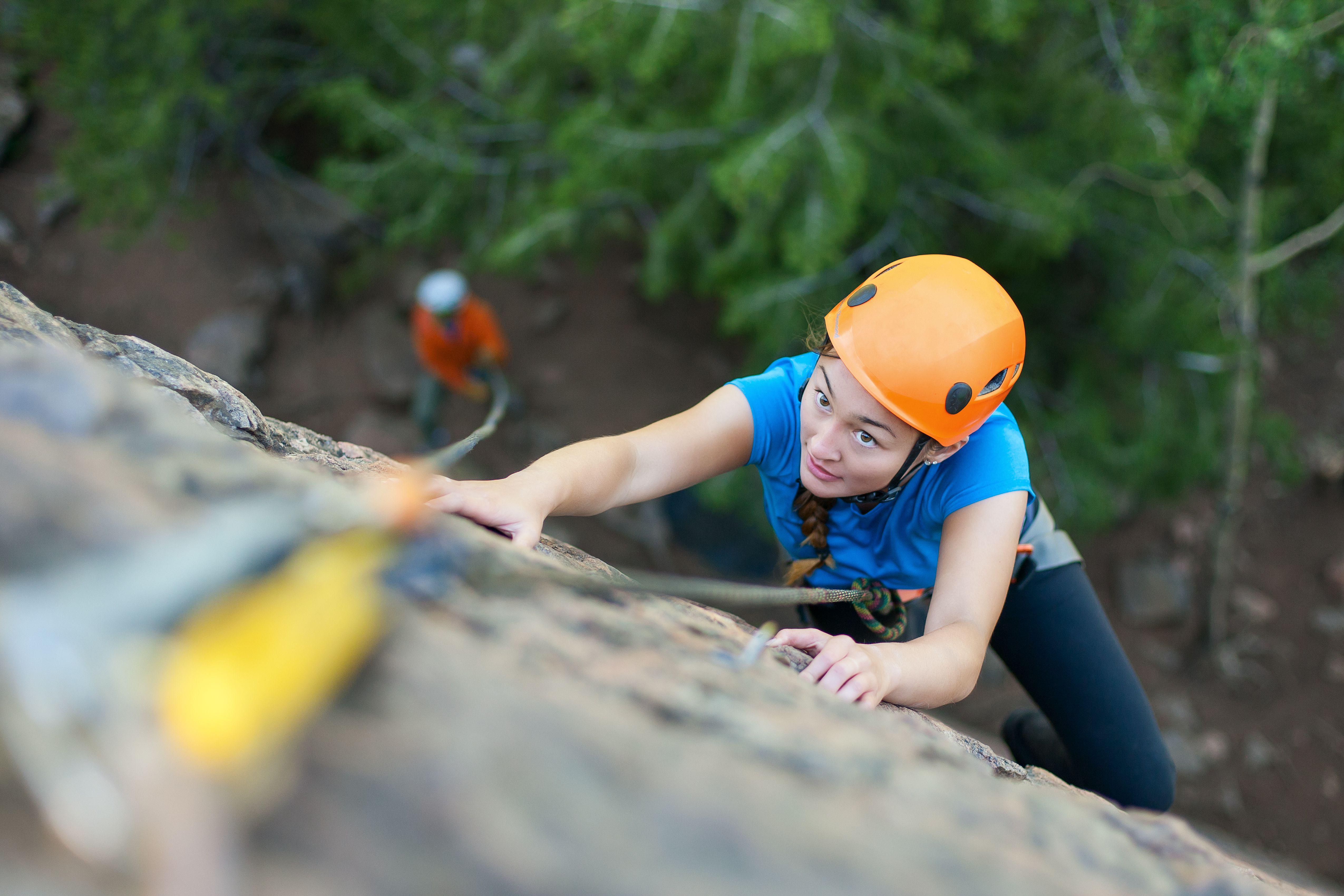 Focused young girl rock climbing.