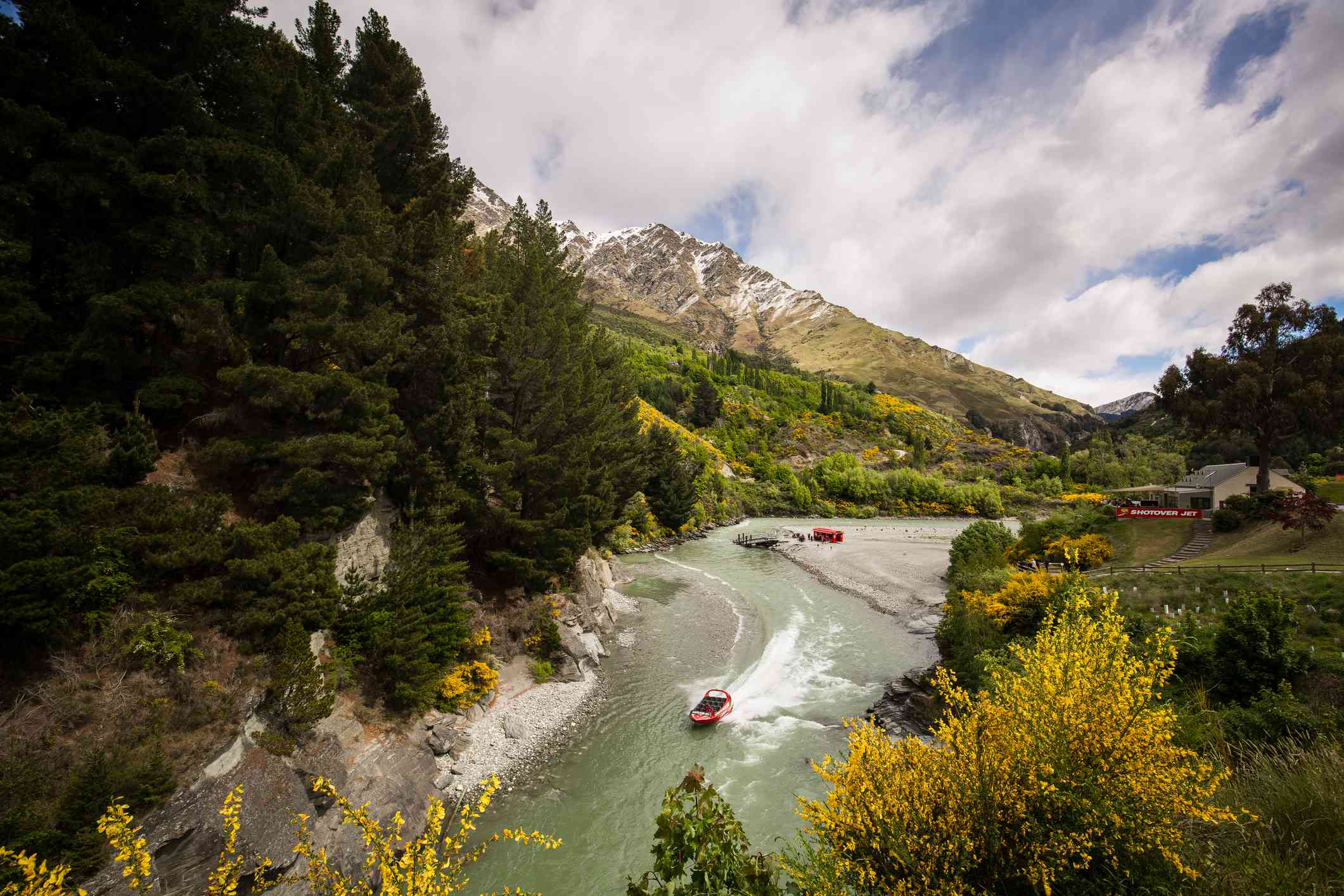 jet boat on a river in a canyon surrounded by trees and mountains
