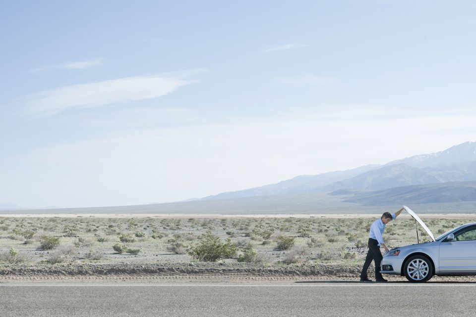 Man with a broken down car in the desert