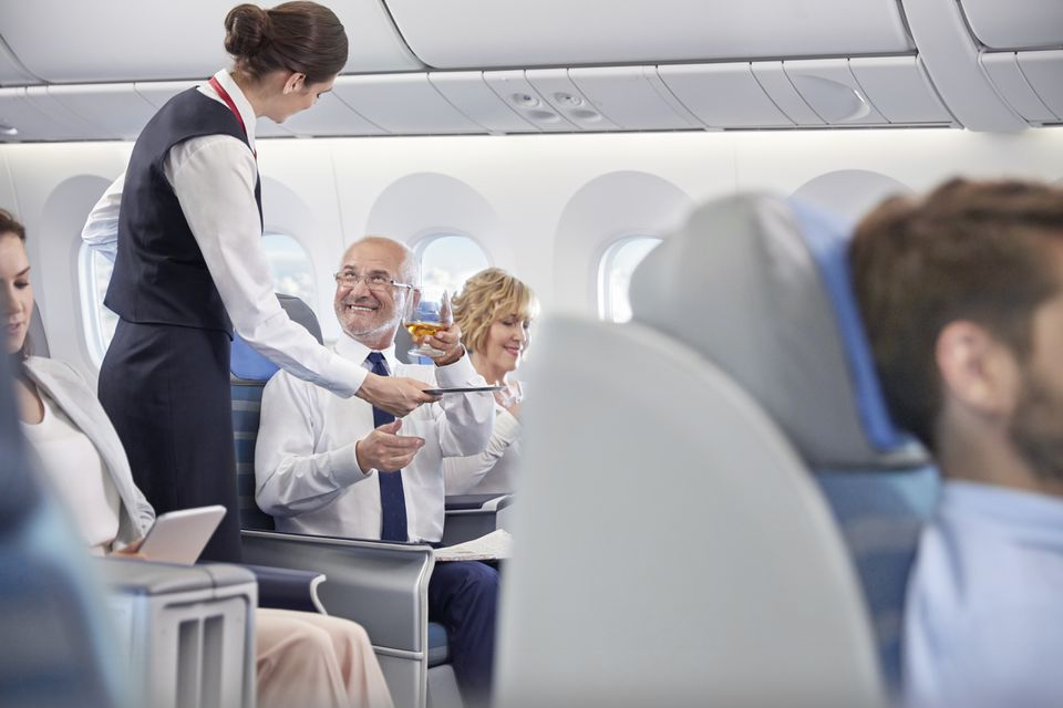 Flight attendant serving whiskey to businessman in first class on airplane