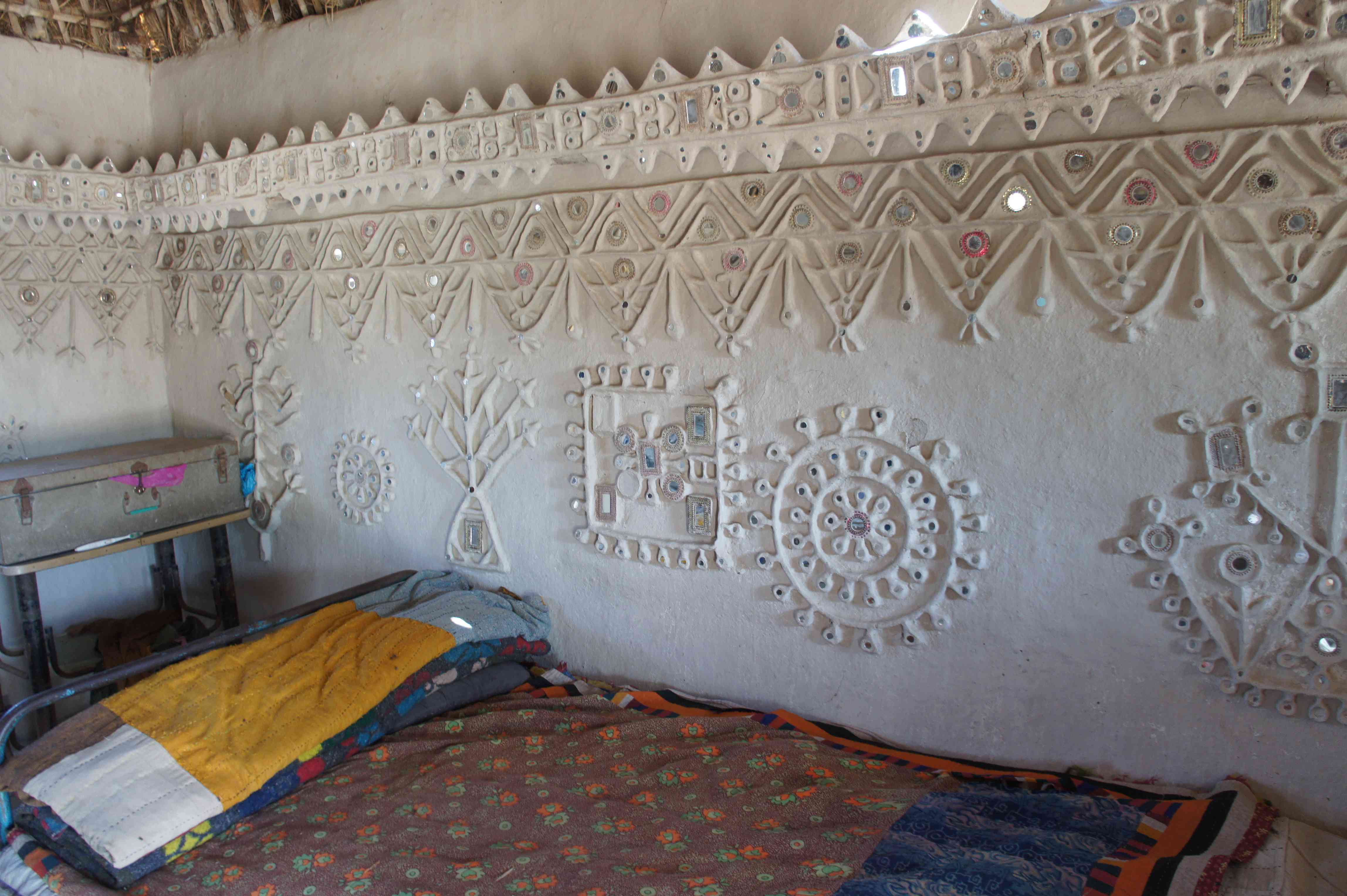 white was wall with clay decorations embellised with small mirrors