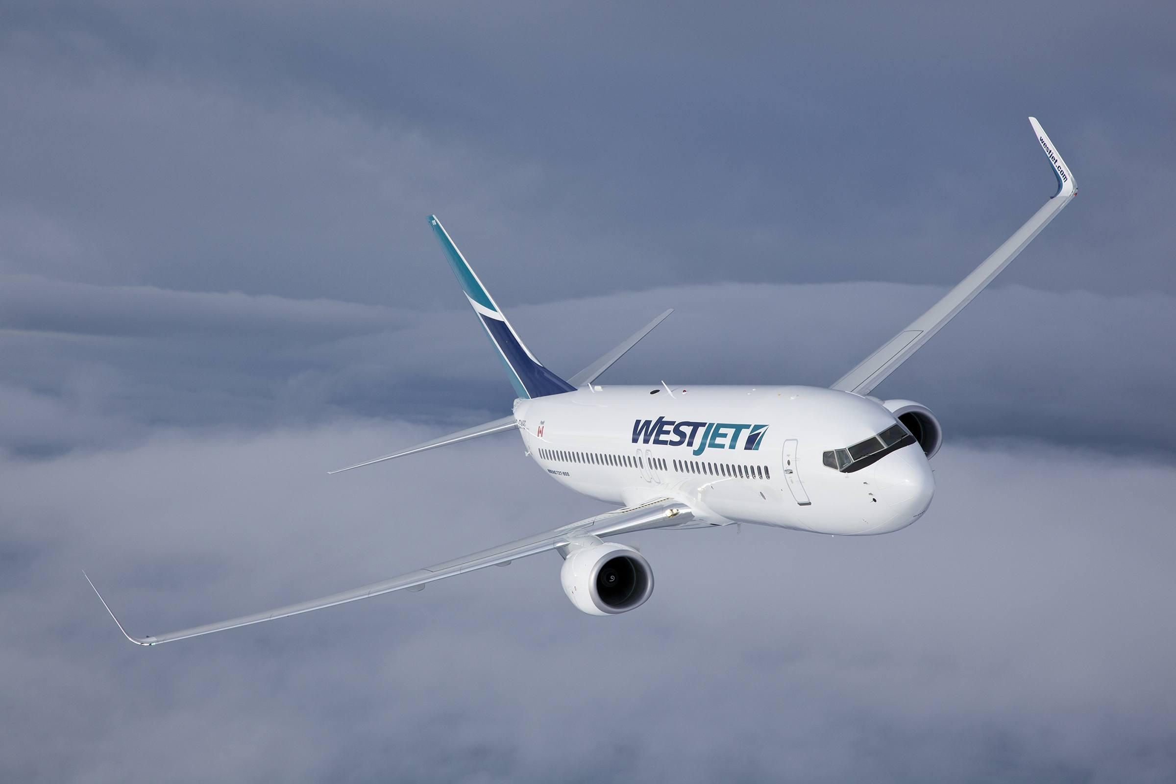 A WestJet plane flies over a cloudy sky