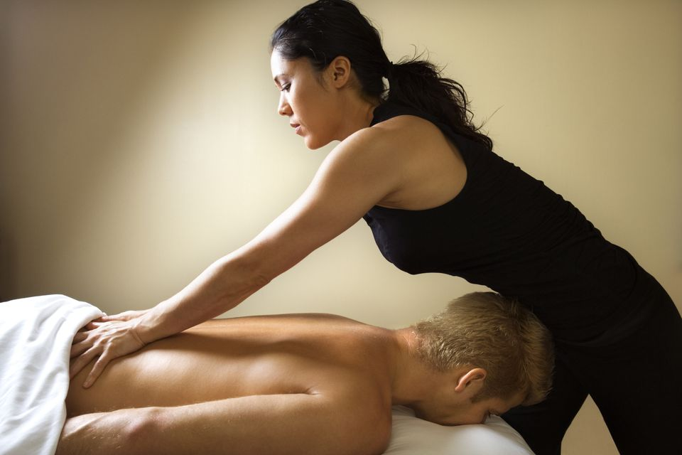Female massage therapist massaging client's back