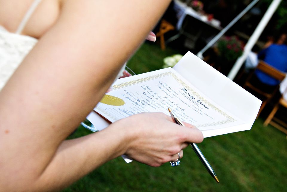 Bride signing her marriage license.