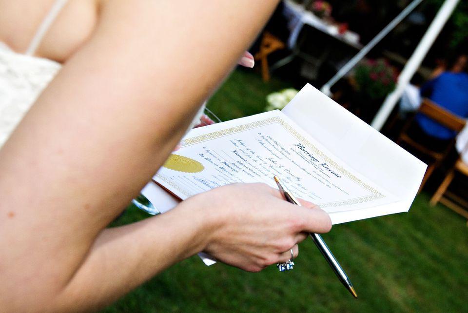 Novia firmando su licencia de matrimonio.