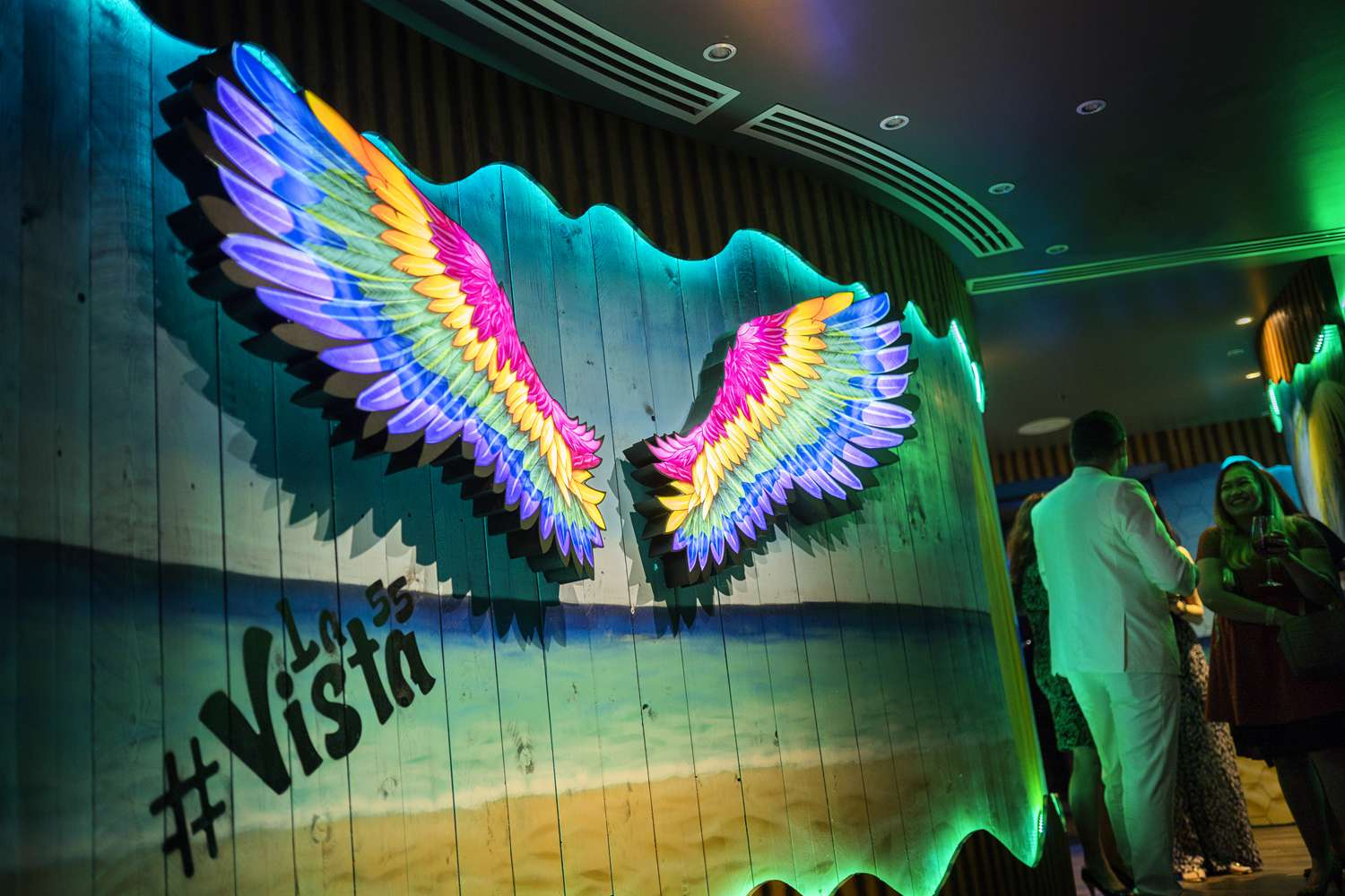 Colorful, illumbinated wings on a wooden wall painted like the beach.