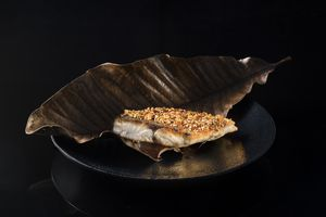 Wok-seared sea bream on a black plate with a large, bronze metal leaf on the plate and under the fish