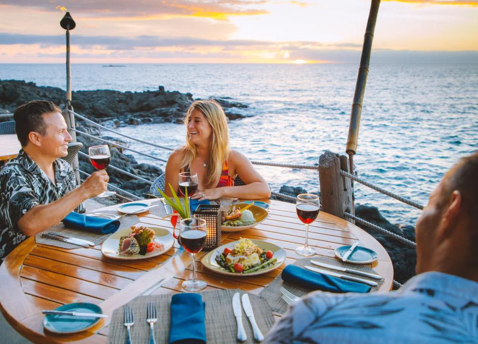a group of people eating dinner with scenic coastal views behind them