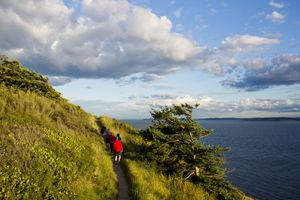 A family hikes along a trail while enjoying the views off the coast of Whidbey Island from Ebey State Park.