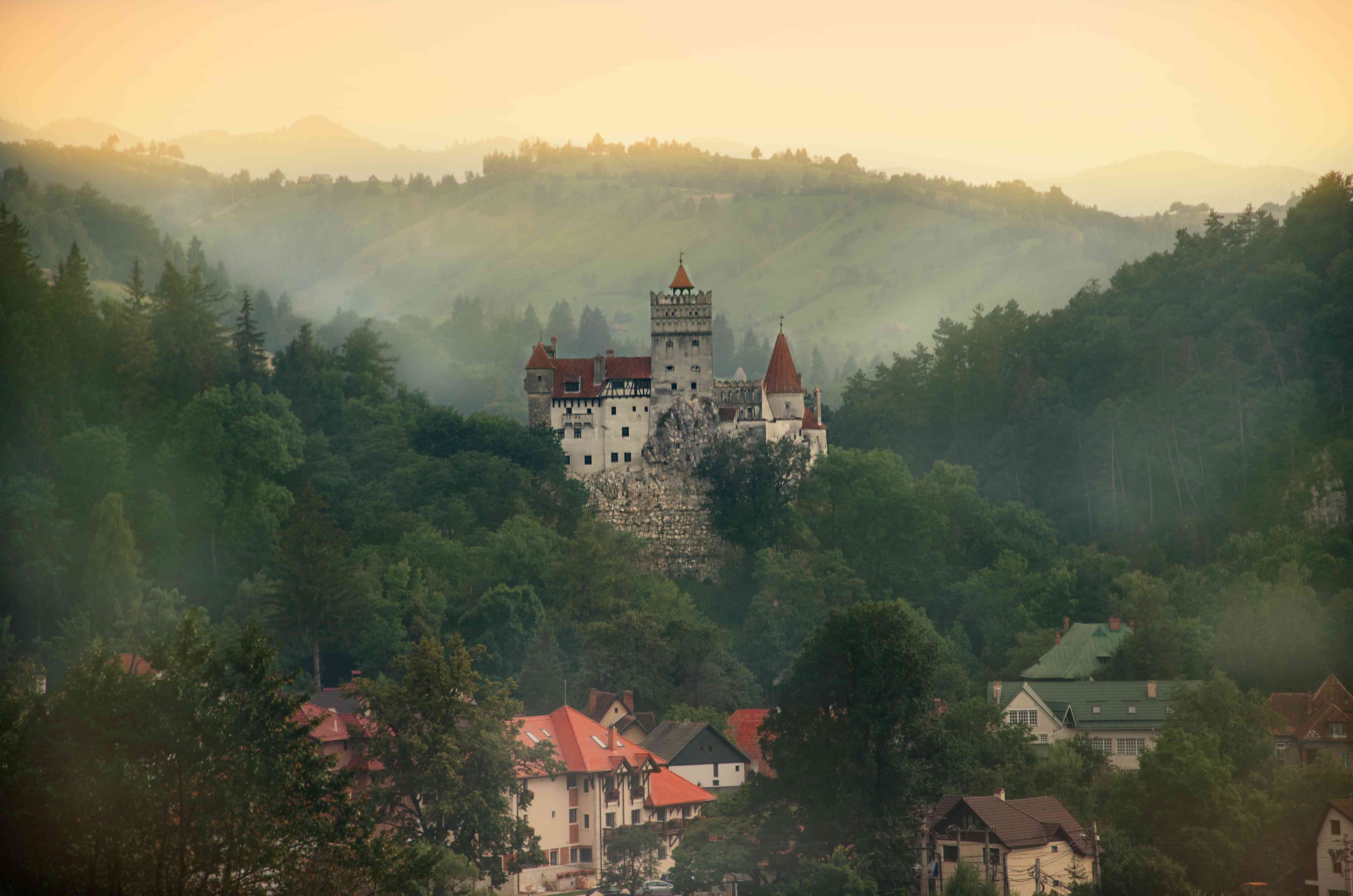 medieval fortress on a hilly landscape above a town on a hazy day