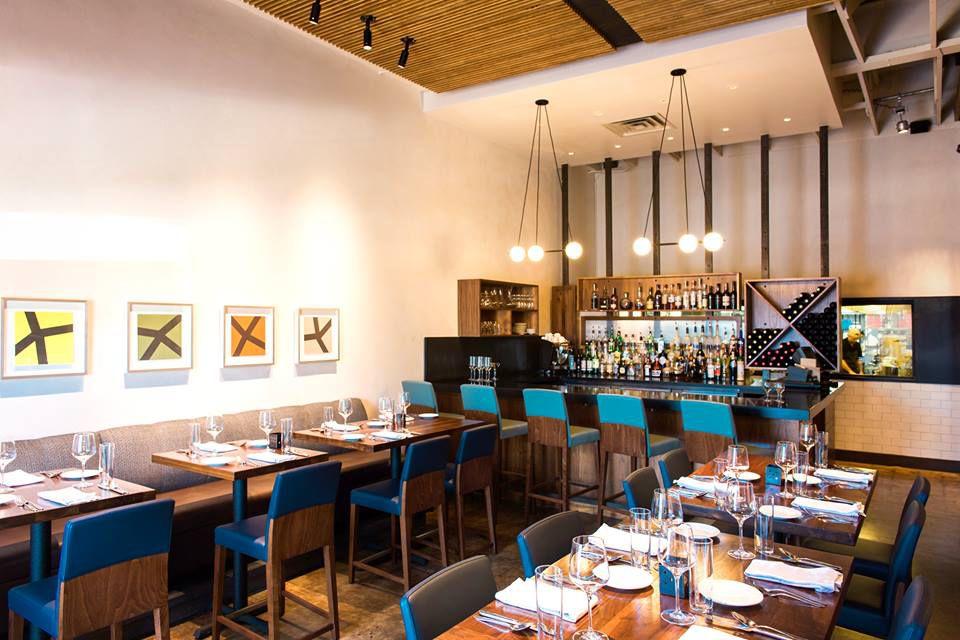 Interior de un restaurante con juego, mesas de madera y una barra corta