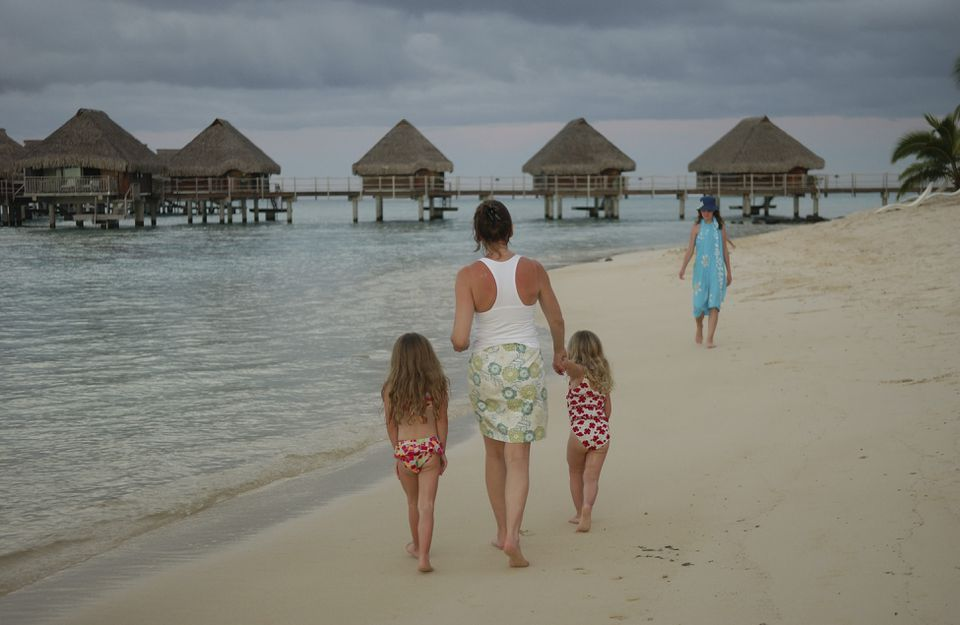 family walking on a beach in Moorea, Tahiti, French Polynesia, South Pacific