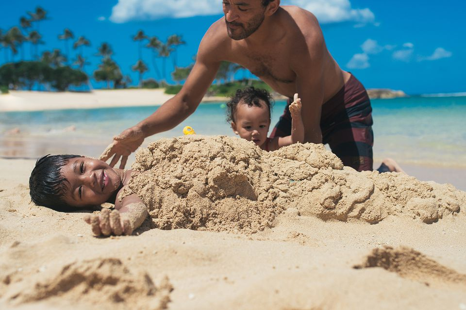 Father and daughter burying son in sand on the beach