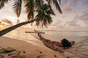 Young adult woman relaxing in the hammock at Maldives