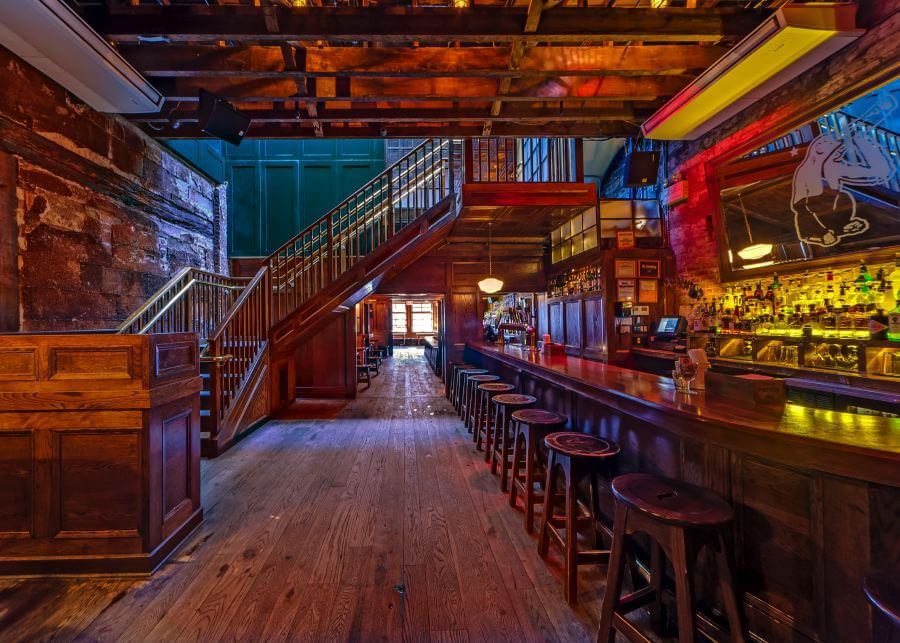 All wooden interiror of a bar, with a long bar with stools on the left side and a staircase leading to a second level on the right
