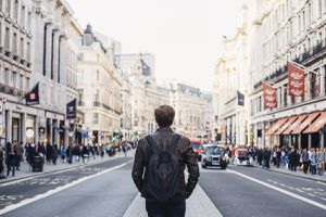 A solo traveler walks down a busy street wearing a backpack