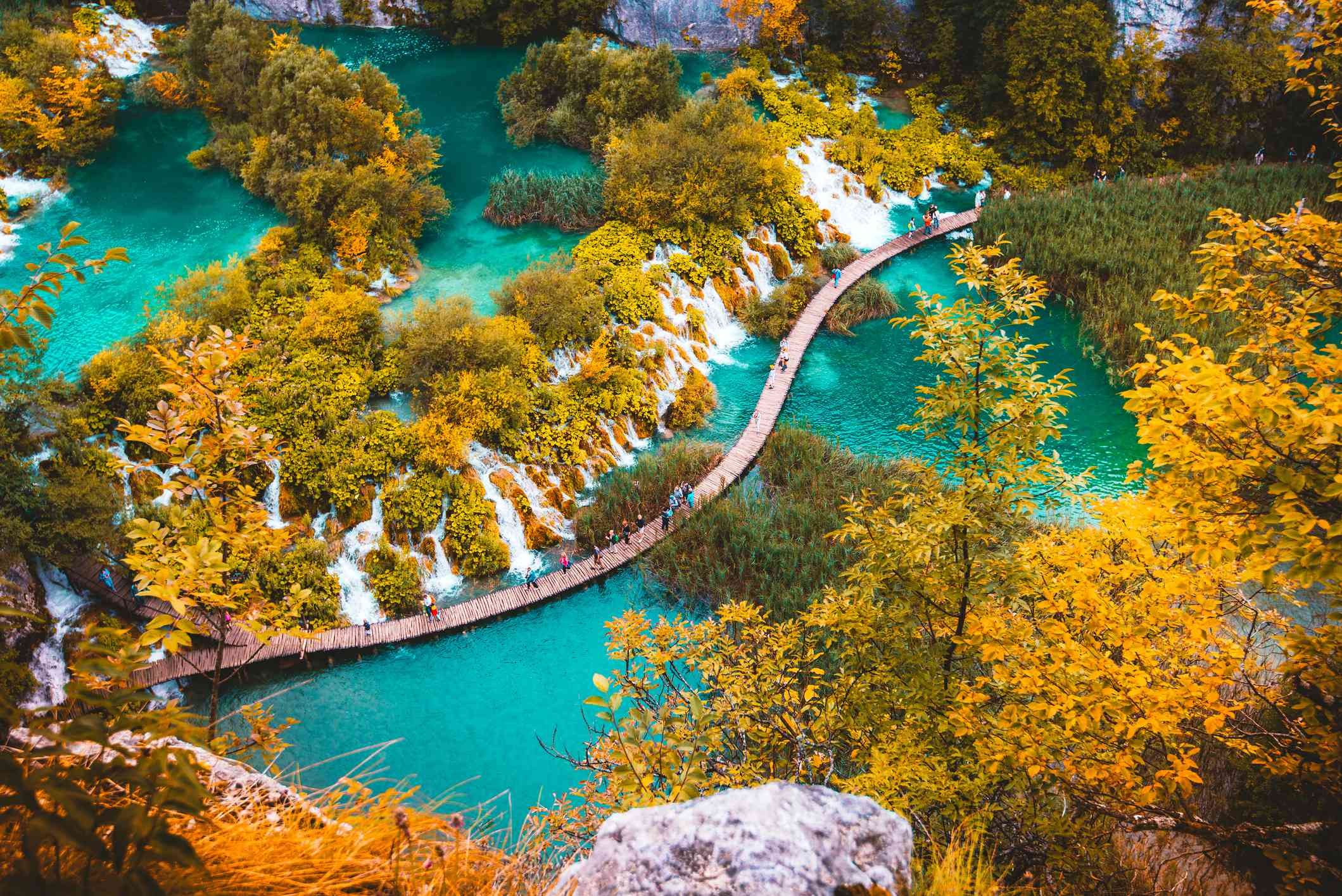 High Angle View Of people walking on a curving path over water with autumn trees