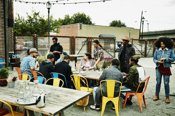 Group of friends hanging out at table at outdoor restaurant sharing drinks and food