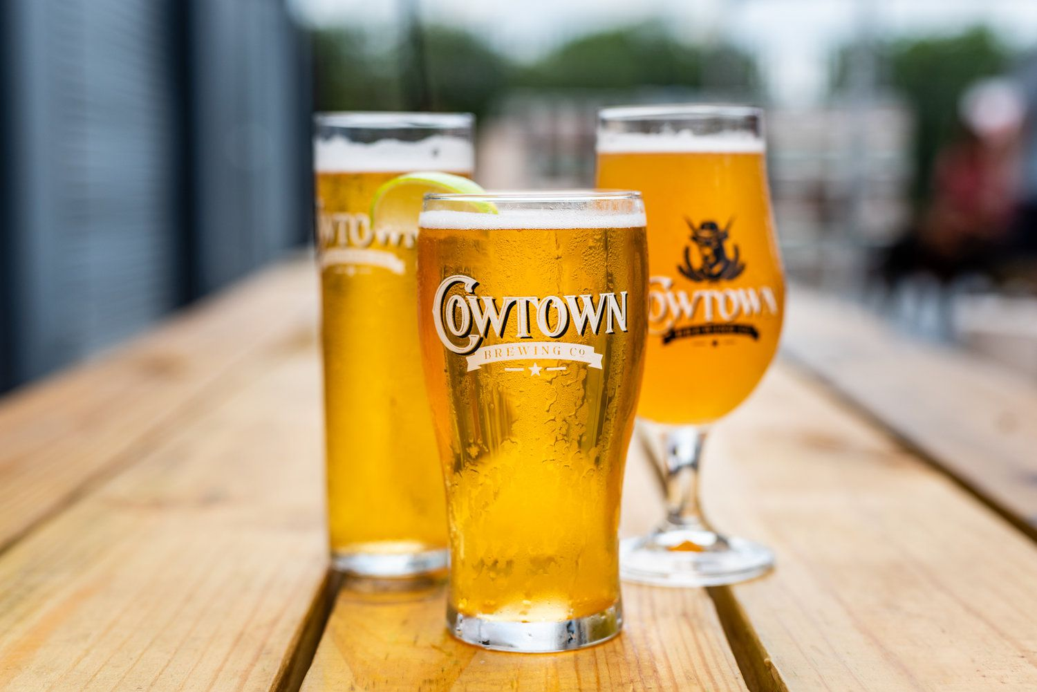 three differently shaped glass of beer on a wooden table arranged with one glass closer to camera