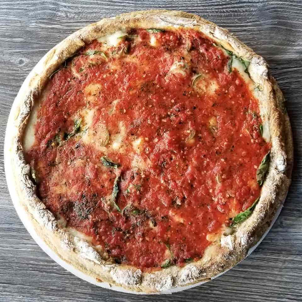 vegan chicago style pizza shot from overhead with a flour-dusted crust and tomato sauce on top