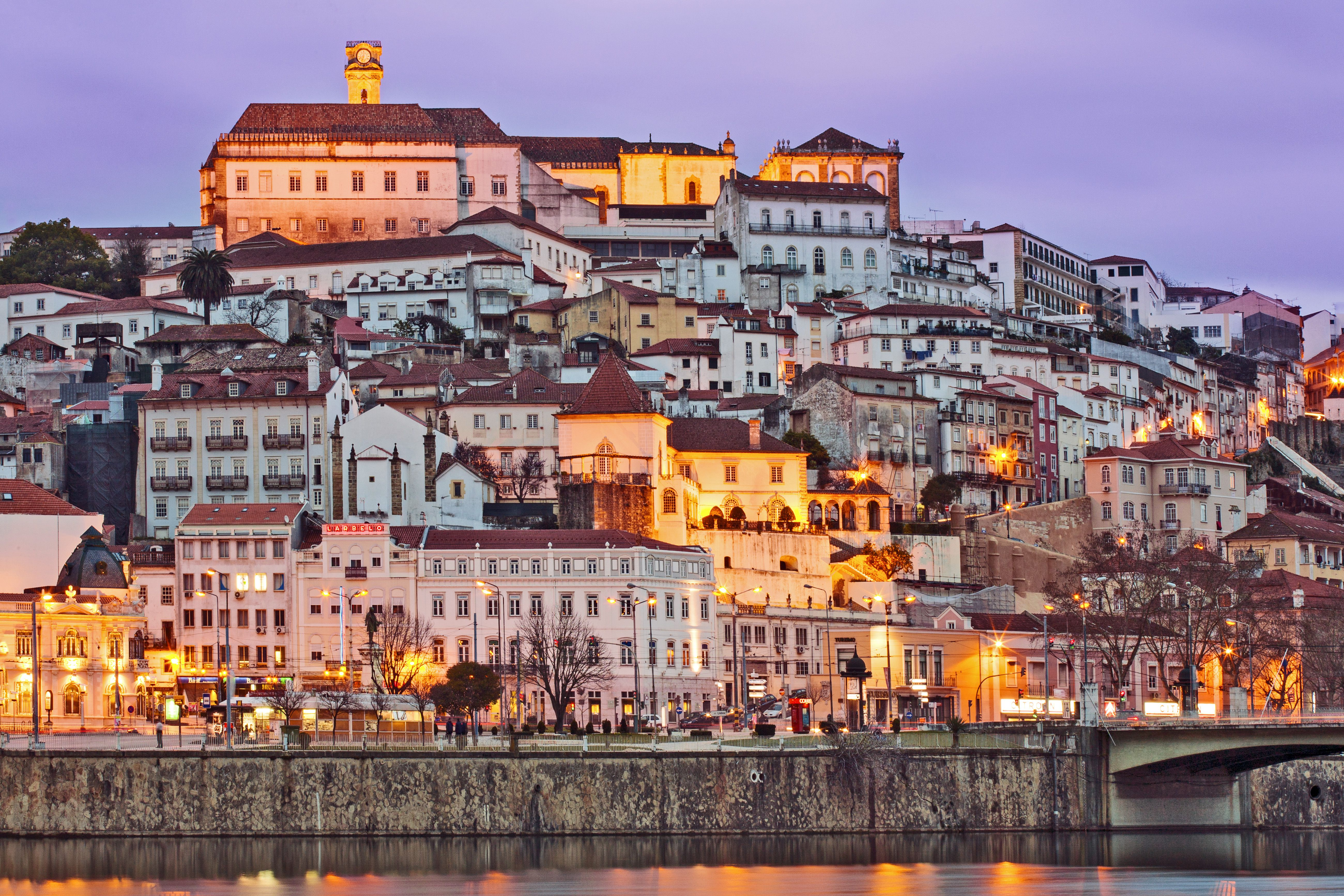 Portugal, Centro, Baixo Mondego, Coimbra, Twilight view of medieval city centre, UNESCO World Heritage listed University of Coimbra-Alta and Sofia (crowning hill), and Mondego river