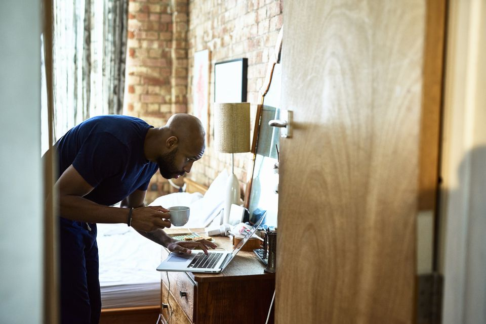 Man with coffee checking emails on laptop in bedroom