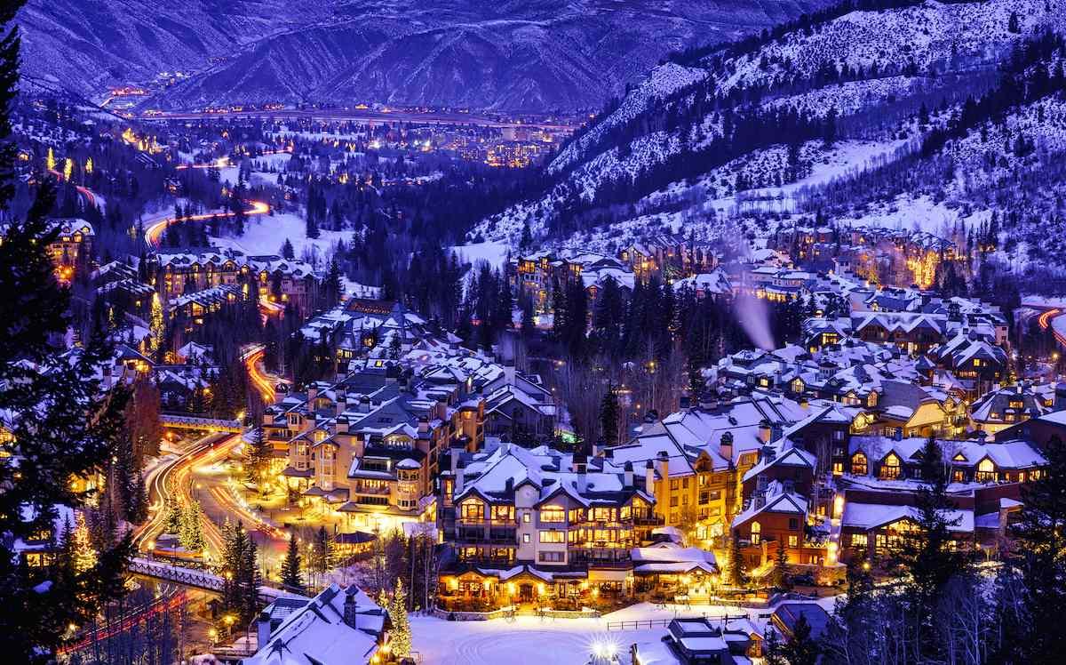A ski lodge lights up a snow Colorado valley at night.