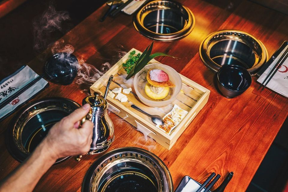 Hand pouring hot water from a kettle onto a bamboo steamer on a table with 4 individual burners