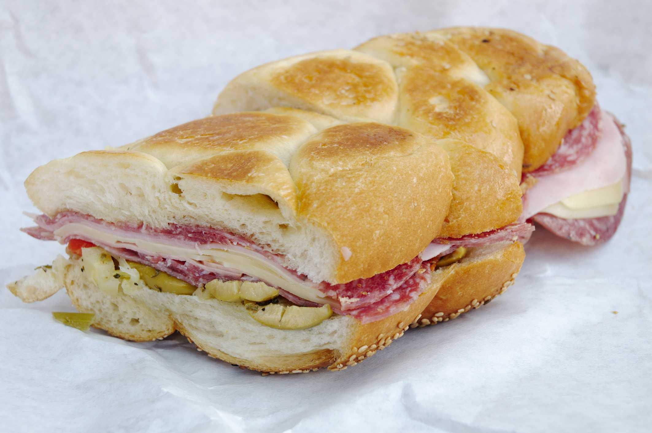 Half a muffuletta sandwich, stuffed with salami, mortadella, cheese, olives