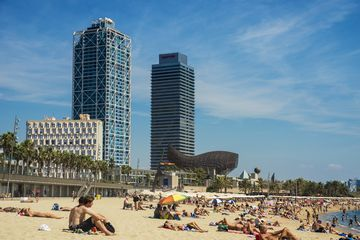 A crowded Barceloneta beach with skyscrapers in the distance