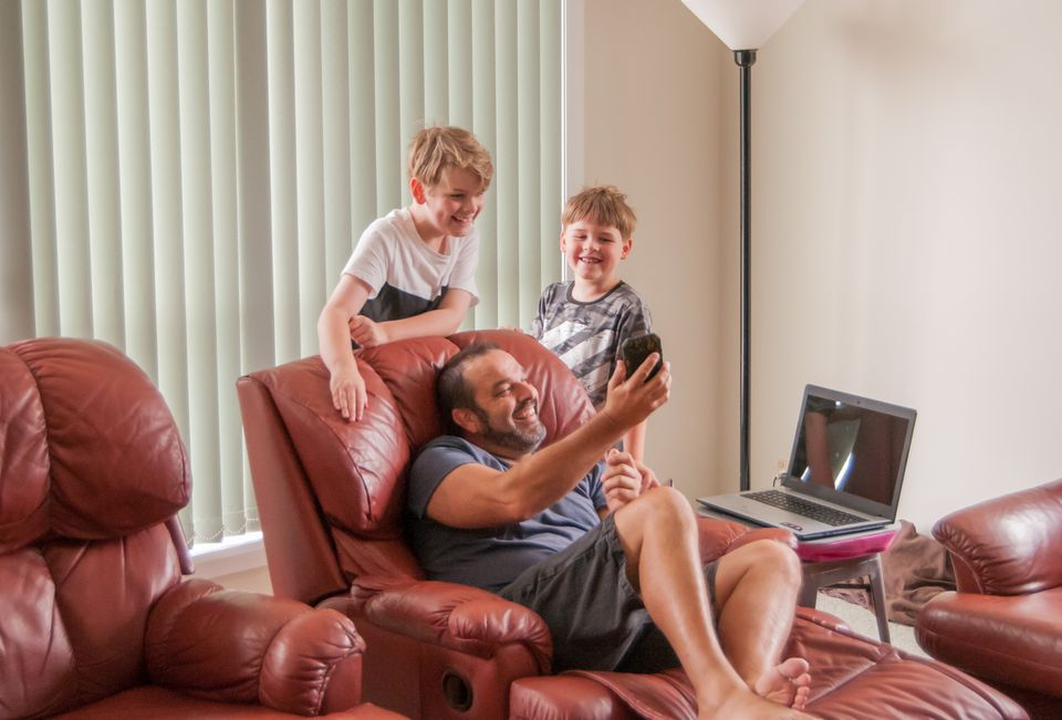 Children looking at device held by man relaxing in recliners