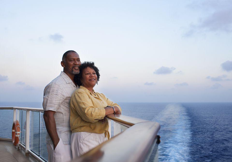 Couple leaning on balcony on cruise