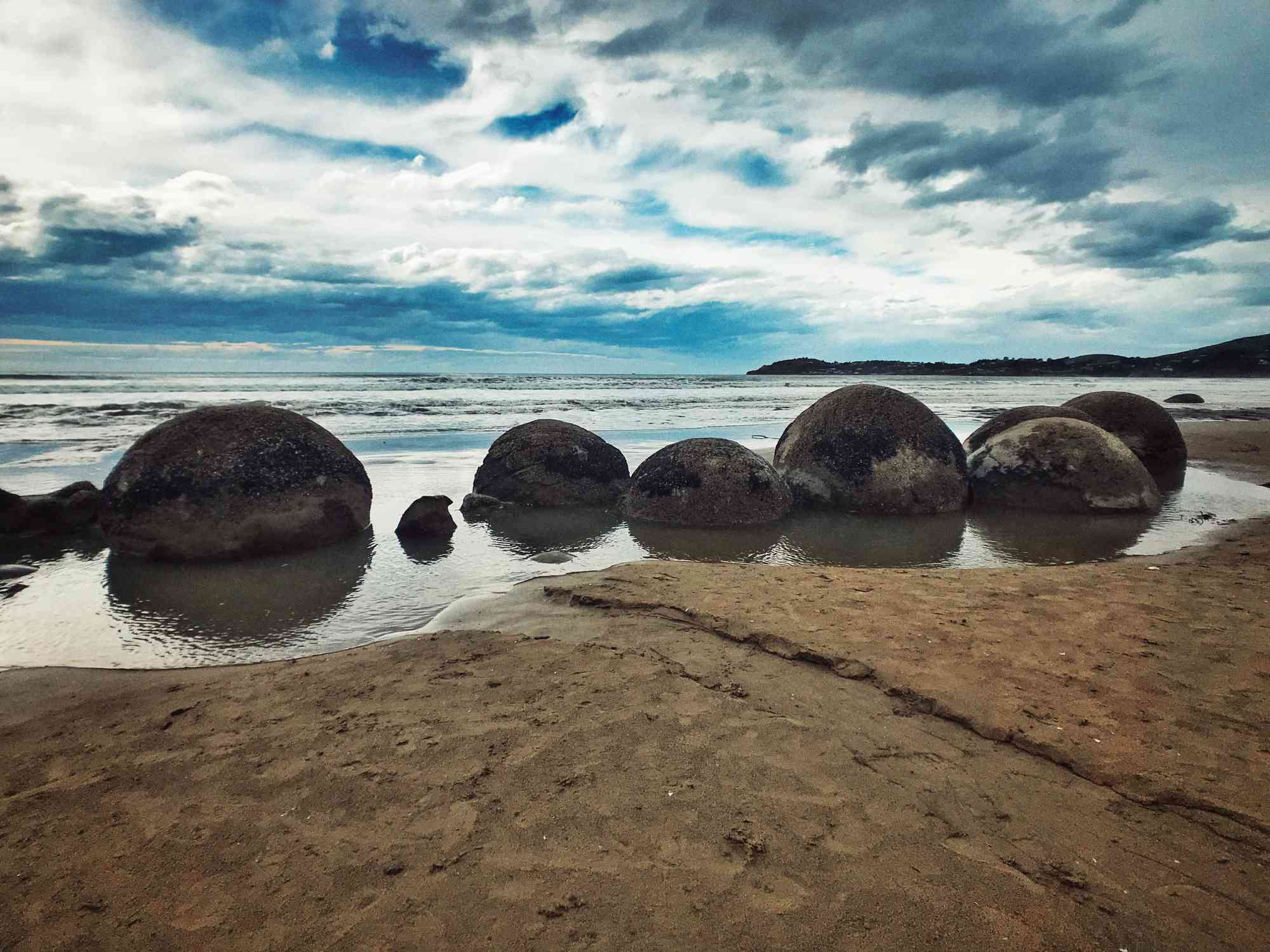 large stone boulders sitting on a beach with sand and sea