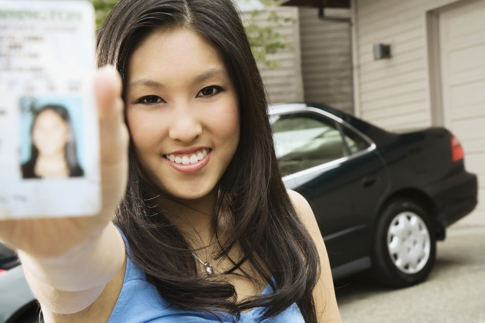 A woman holds up her driver's license