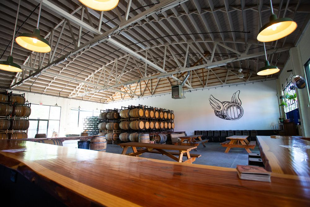view of empty beer taproom with a curved industrial roof and hanging lights. there are dozens of large barrels in one corners and three wooden picnic tables. The picture is taken from behind a polished wood bar