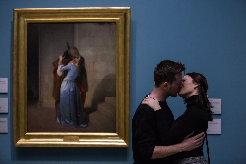 A couple kisses in front of Francesco Hayez's masterpiece 'The Kiss' at Pinacoteca di Brera (Brera Art Gallery) on February 14, 2018 in Milan, Italy.