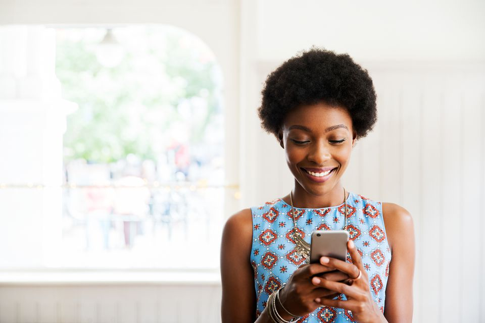 Woman smiling using smart phone