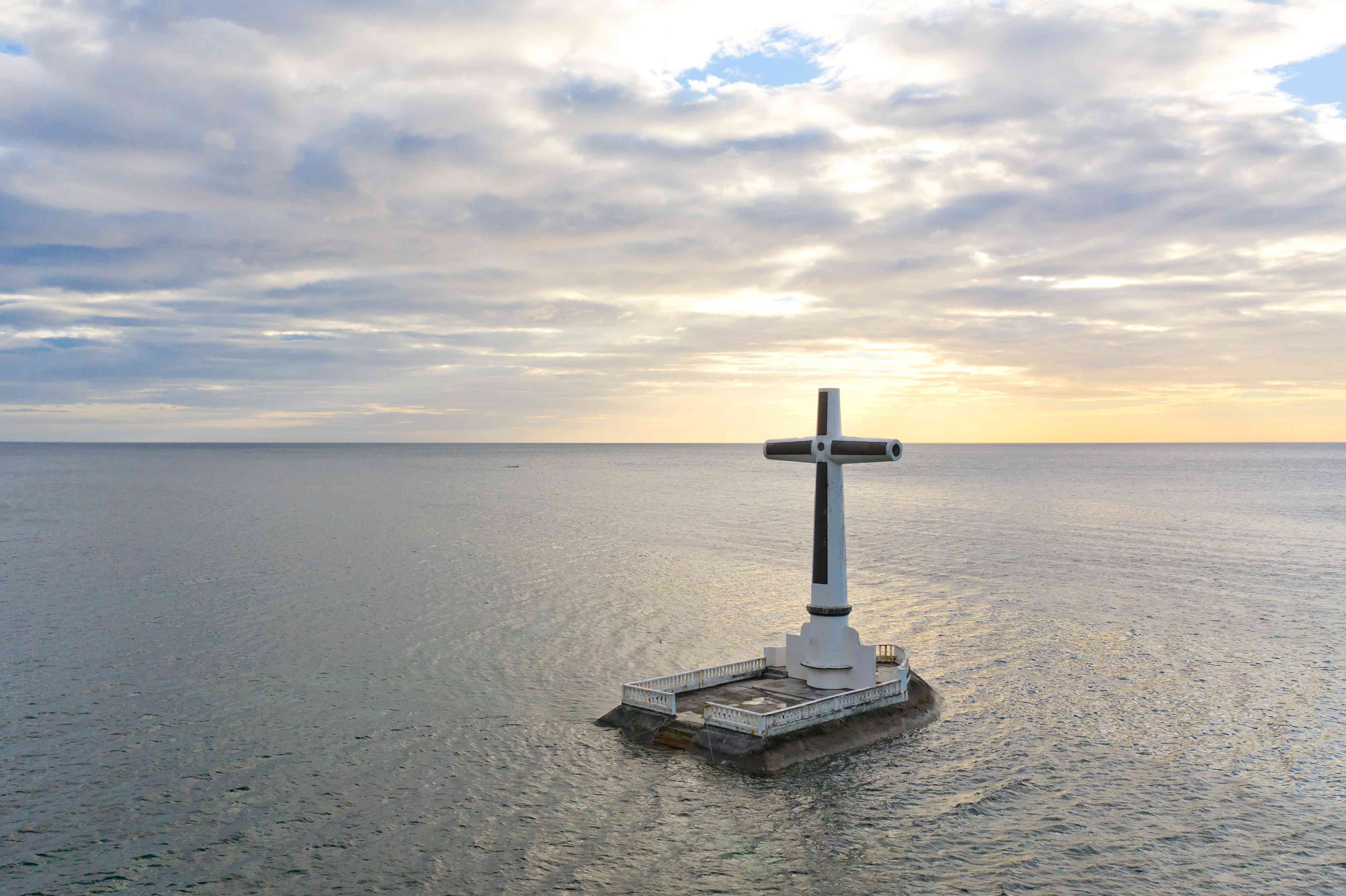 Catholic cross in a flooded cemetery in the sea near the island of Camiguin