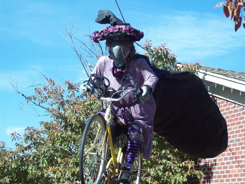 Bruja montando una bicicleta Exhibición de Halloween en Gardner's Village
