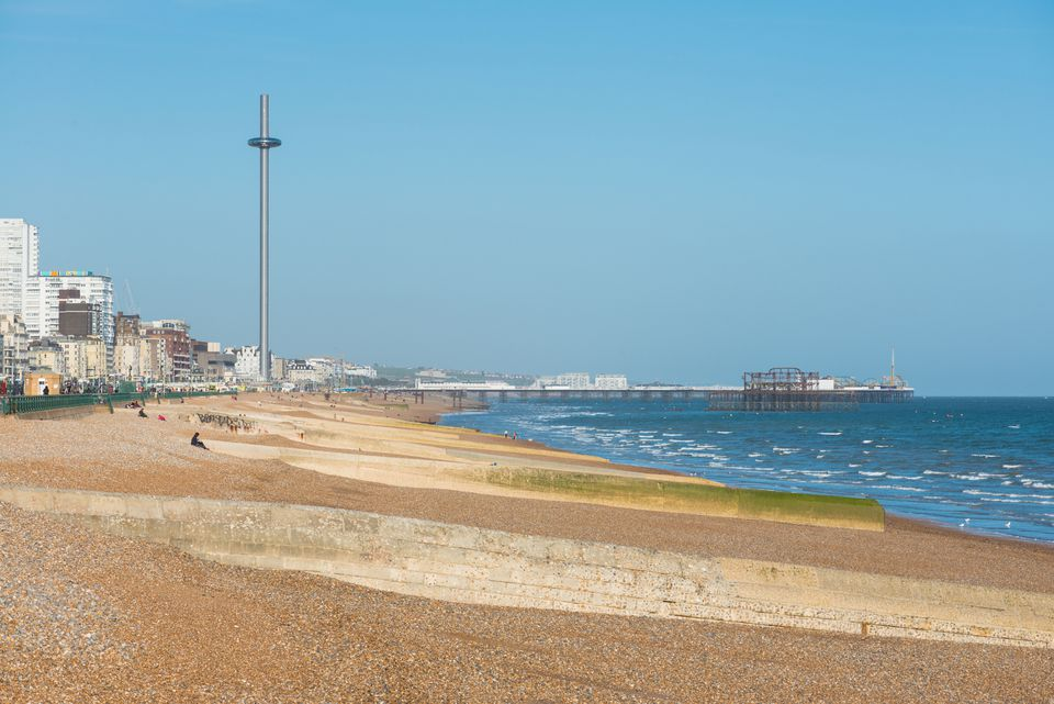 View along the beach at Brighton towards the Palace Pier and i360 Tower.