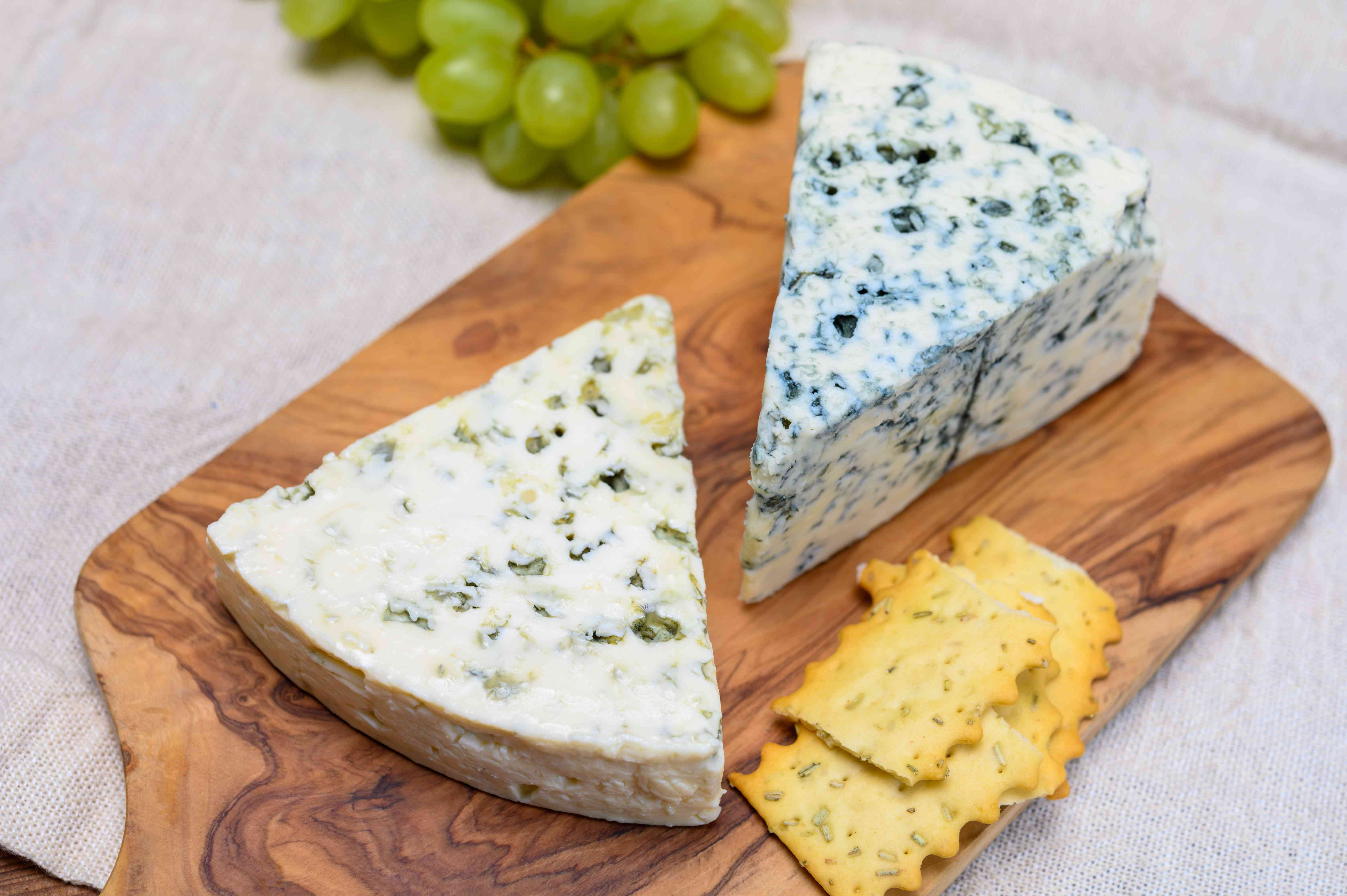 Danish blue cheeses on a board with some crackers and green grapes in the background