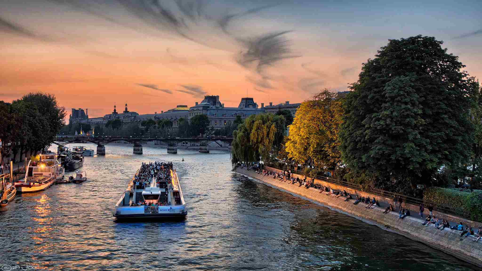 A boat going own the Seine River at sunset