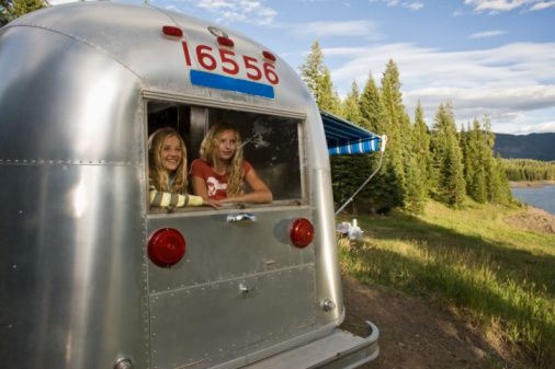 Sisters camping in Airstream travel trailer next to a lake in Montana.