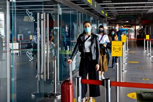 Passengers wearing N95 face masks waiting in line at airport terminal