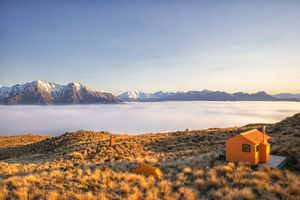 orange hut and orange tent in a grassy field at sunset. There are mountains in the background and the field is above the cloud layer