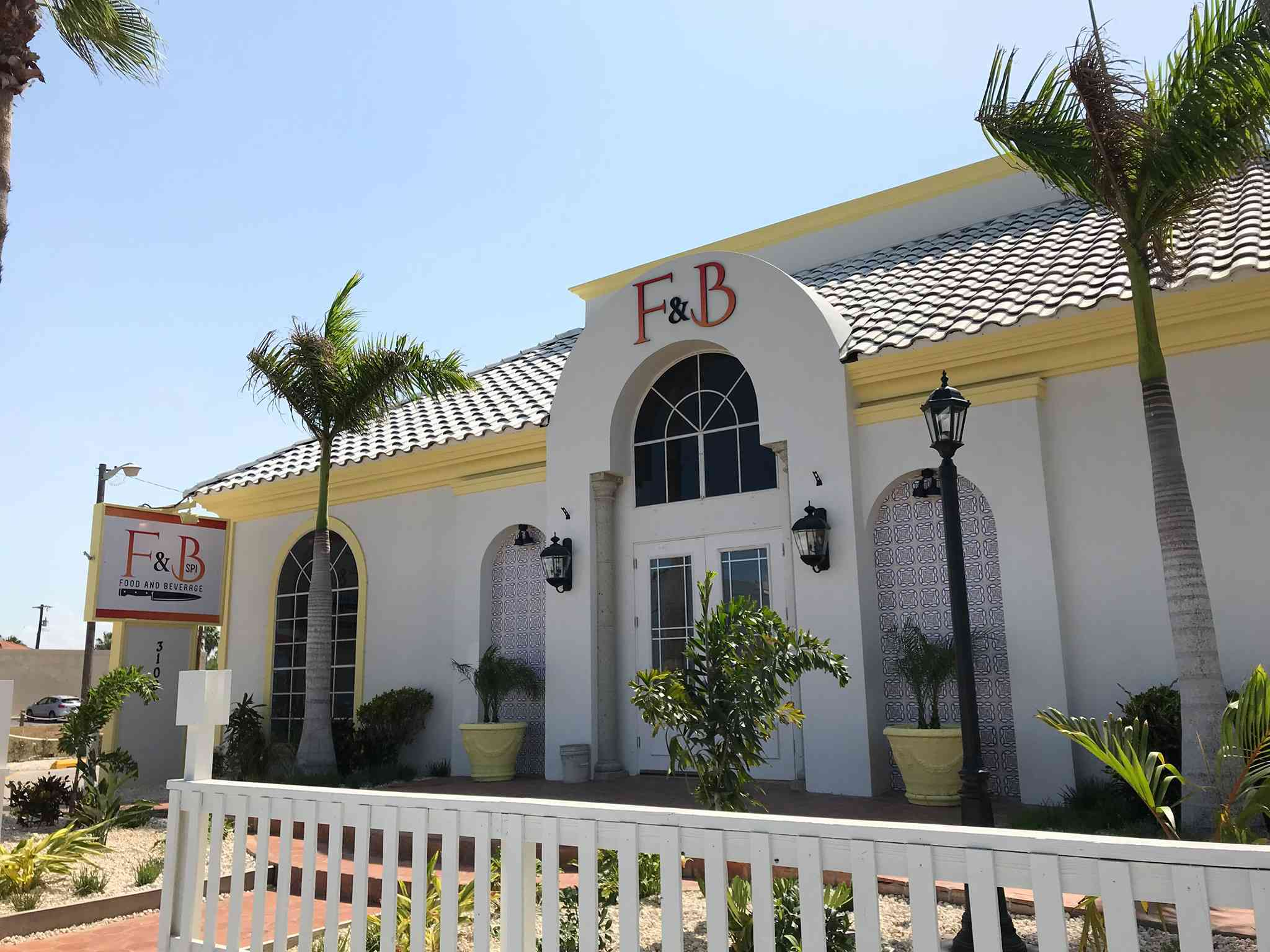 The outside of F&B, a cheery white building with yellow trim, flanked by palm trees