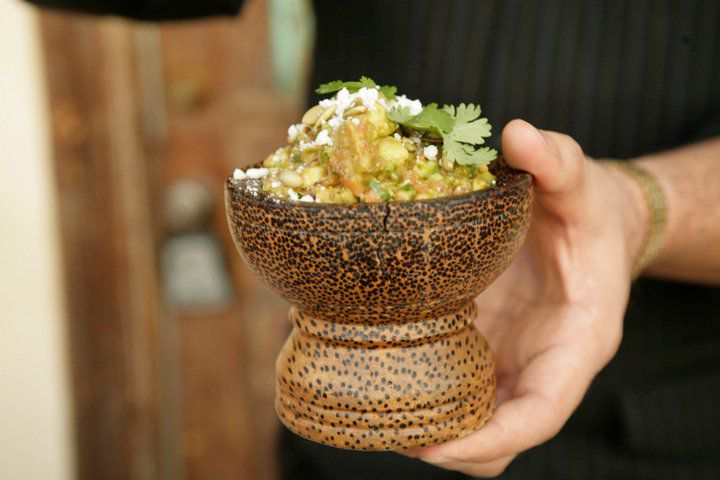 Man holding wooden bowl with filled with guacamole that is topped with cilantro